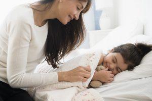 mujer poniendo a niño a la cama