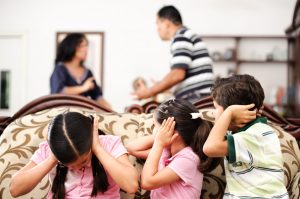 children covering their ears with parents fighting
